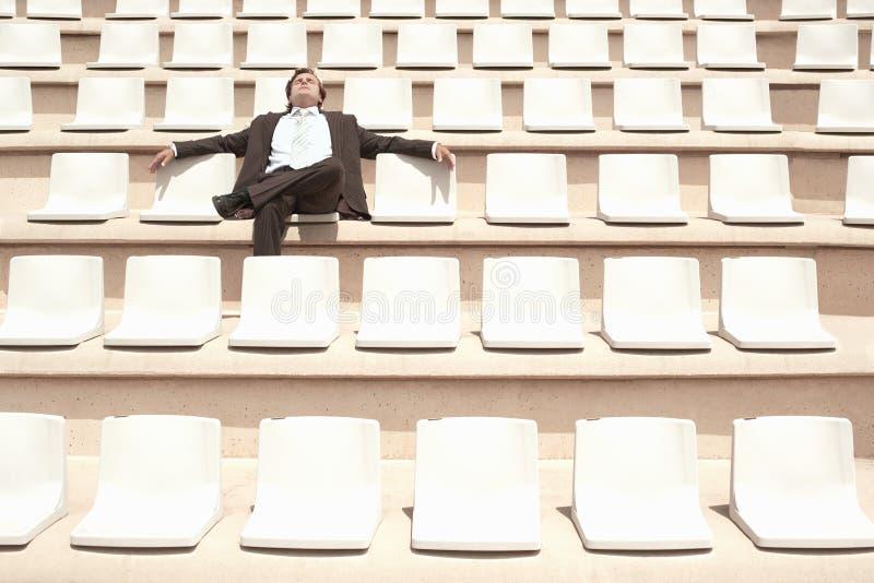 放松在空的观众席的中心的商人 免版税库存图片