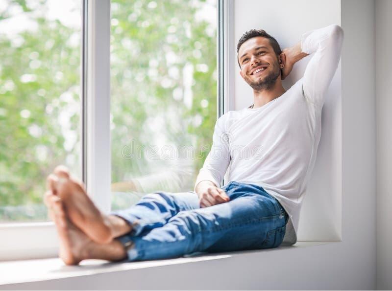 放松在窗口基石的英俊的微笑的人 免版税库存照片