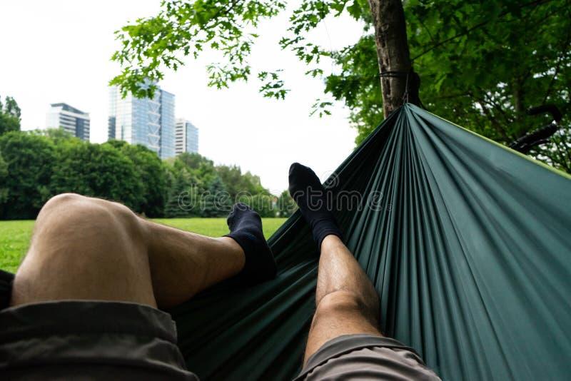 放松在绿色吊床在夏天在城市公园 袜子在脚关闭  大厦和草背景 人腿 免版税库存图片