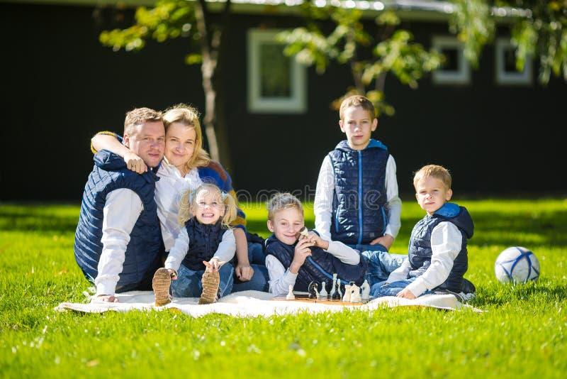 放松在绿色自然的大家庭 在室外的幸福家庭画象,小组六人坐草,夏季 免版税库存照片