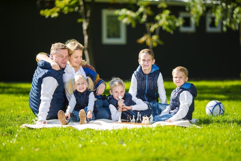 放松在绿色自然的大家庭 在室外的幸福家庭画象,小组六人坐草,夏季 库存照片