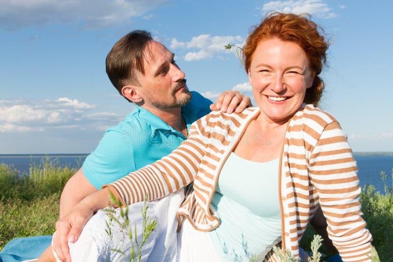 放松在绿草和蓝天的愉快的微笑的夫妇 说谎在草的年轻夫妇室外有水和天空背景 图库摄影