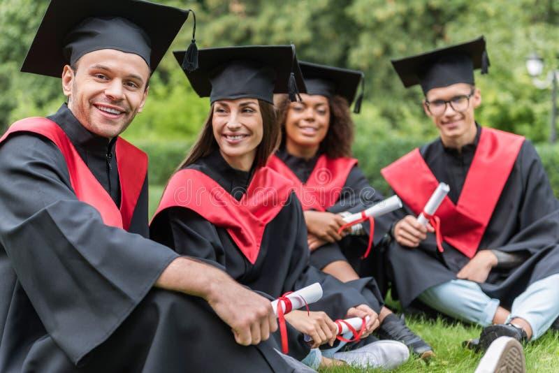 放松在绿草的快乐的毕业生在校园里 免版税图库摄影