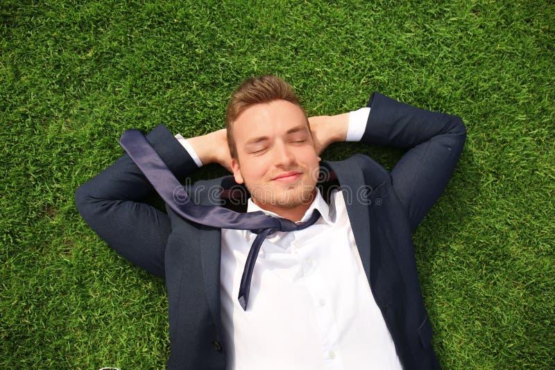 放松在绿草的正装的年轻人户外 库存照片