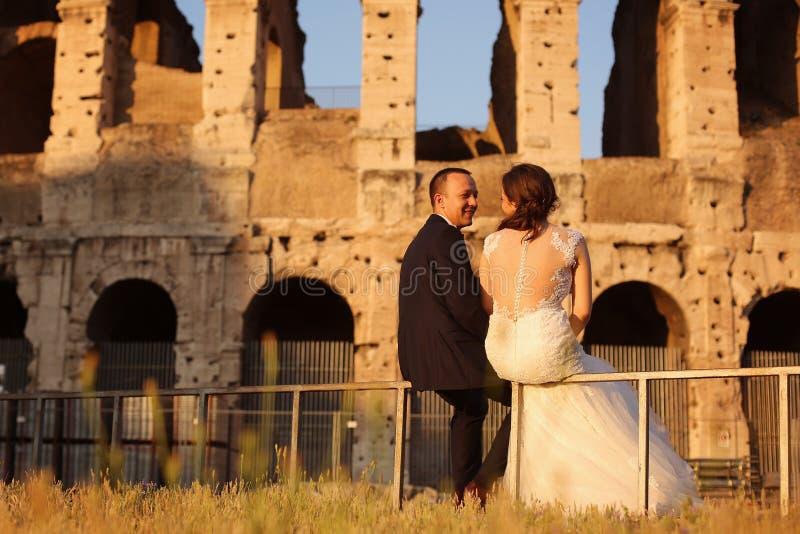 放松在罗马斗兽场附近的美好的新娘夫妇在罗马 免版税库存图片