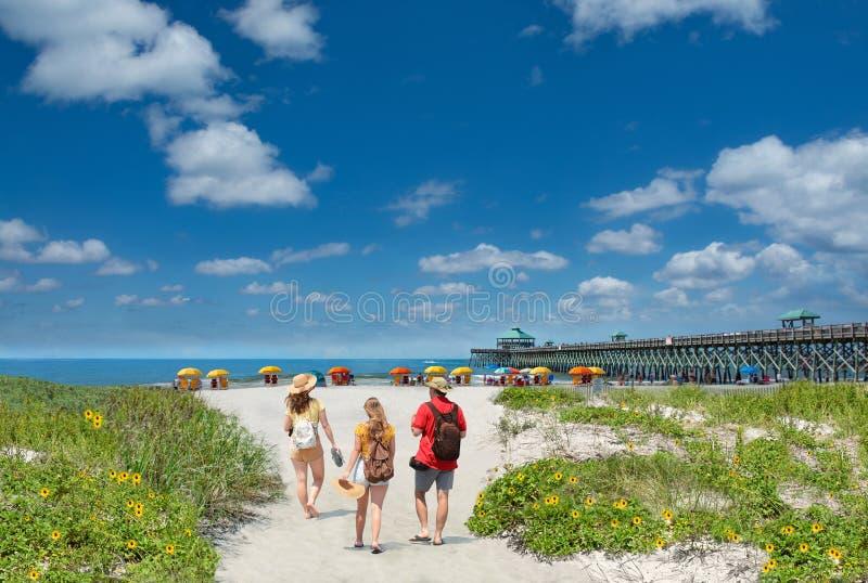 放松在美丽的海滩的家庭在度假暑假 免版税库存照片