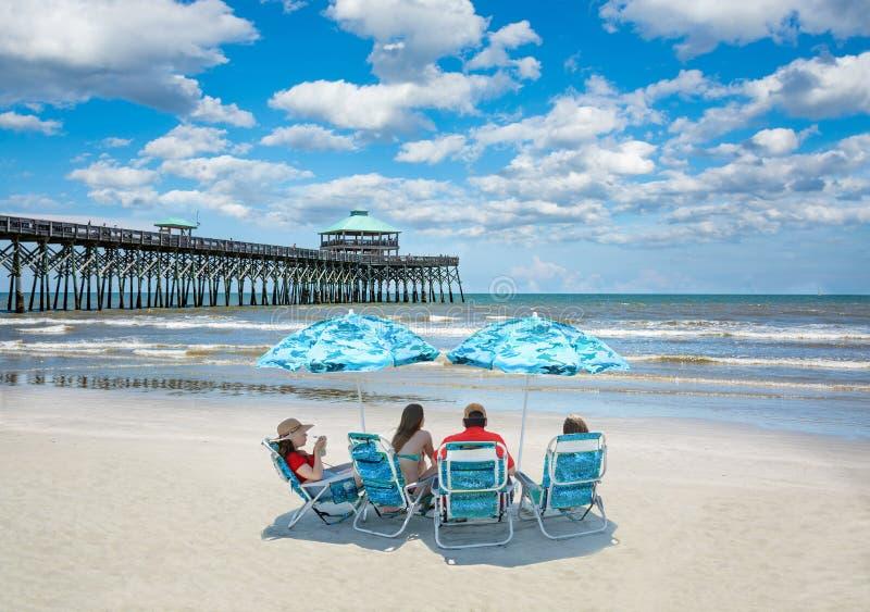放松在美丽的海滩的家庭在度假暑假 图库摄影