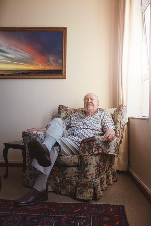 放松在胳膊的老人在家主持 库存图片