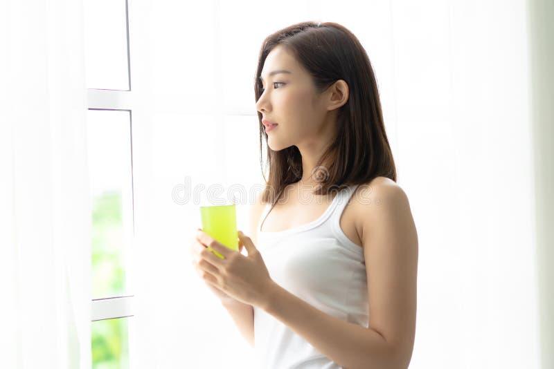 放松在舒适家的年轻快乐的亚裔妇女,感到愉快,r 免版税图库摄影