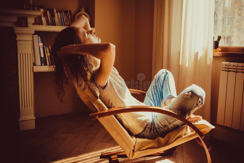 放松在舒适的现代椅子的工作以后的妇女在窗口附近在客厅 温暖的自然光 舒适家 便衣 C 库存照片