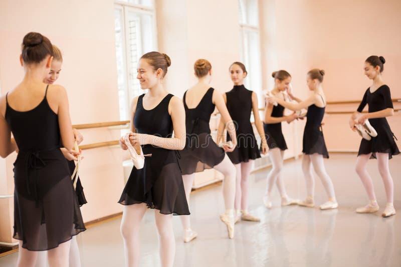 放松在芭蕾类以后的中等小组十几岁的女孩 免版税库存图片