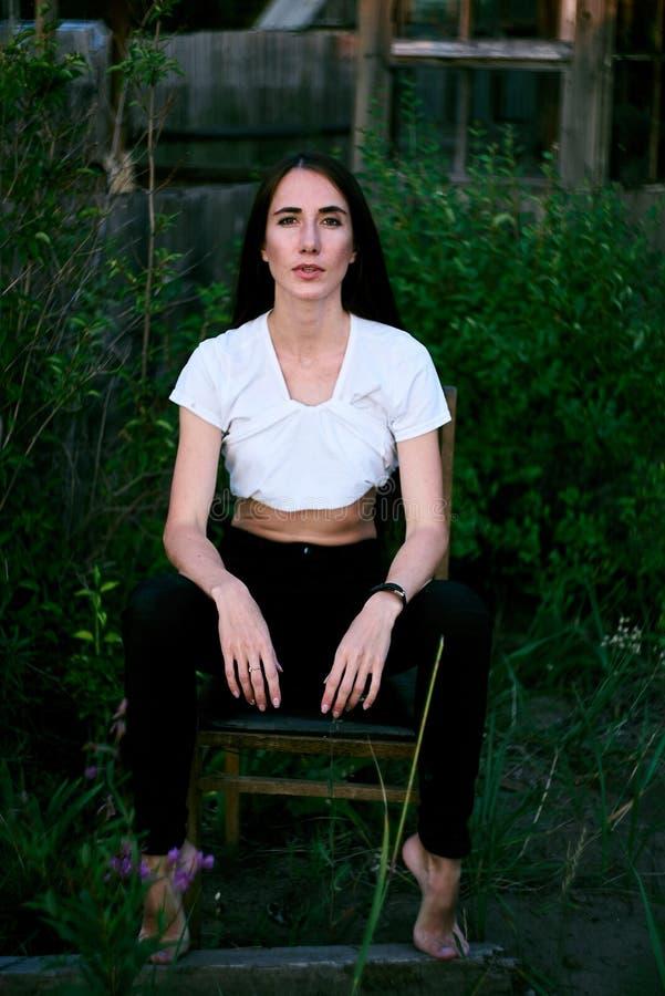 放松在草甸的可爱的深色的女实业家 库存照片