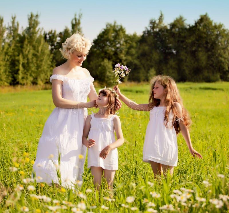 放松在草甸的母亲和女儿 库存照片