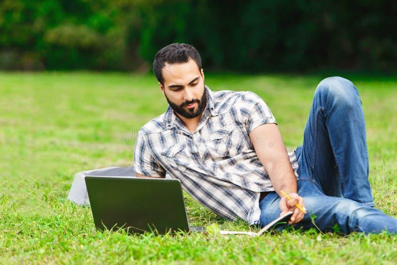 放松在草的有胡子的学生人 免版税库存照片
