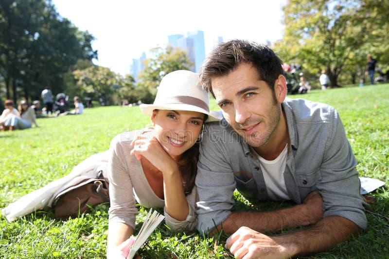 放松在草的年轻夫妇在纽约中央公园 库存图片