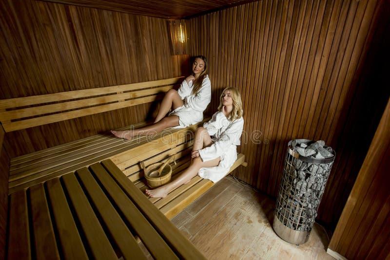放松在蒸汽浴的两年轻女人 免版税库存图片