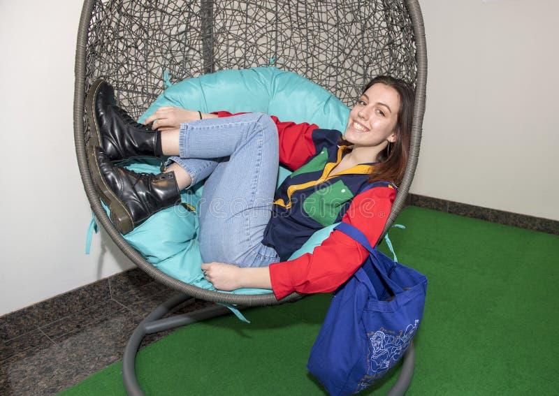 放松在蛋椅子的熟悉内情的十七岁的女孩 库存图片
