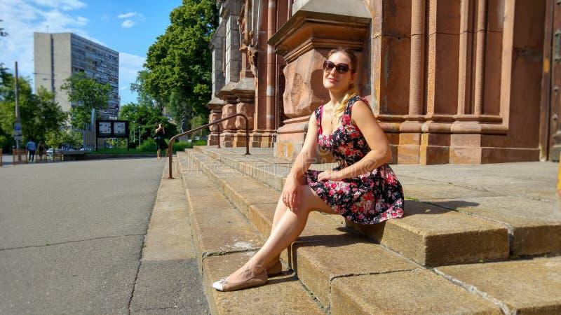 放松在街道上的老石台阶的年轻微笑的妇女佩带的太阳镜的图象 免版税库存图片