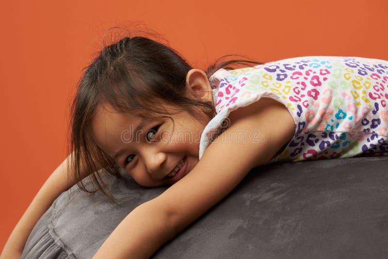 放松在装豆子小布袋的亚洲孩子 免版税库存图片