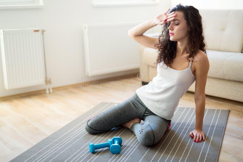 放松在训练以后的年轻疲乏的健身妇女 免版税库存图片