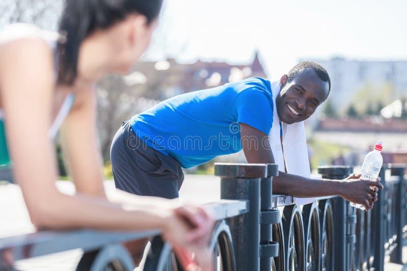 放松在跑步以后的夫妇。年轻人种间夫妇身分 库存图片