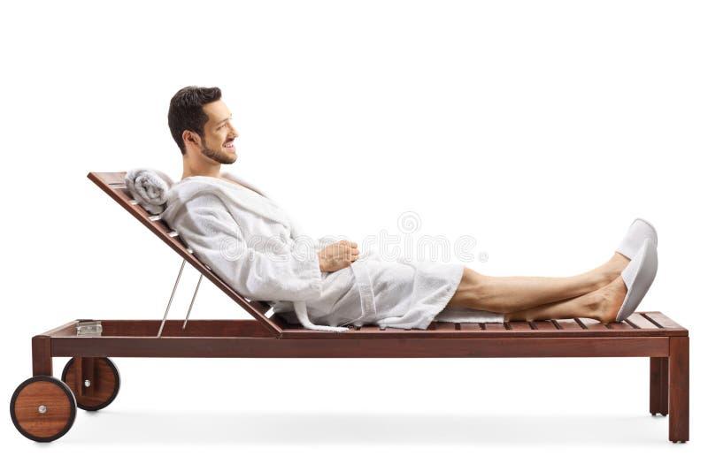 放松在躺椅的浴巾的年轻人 免版税库存照片