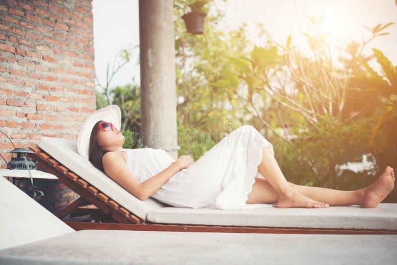 放松在轻便折叠躺椅户外w的迷人的妇女画象 免版税库存图片