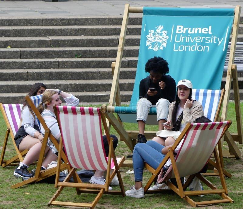 放松在轻便折叠躺椅的学生在布鲁内尔大学伦敦 免版税图库摄影