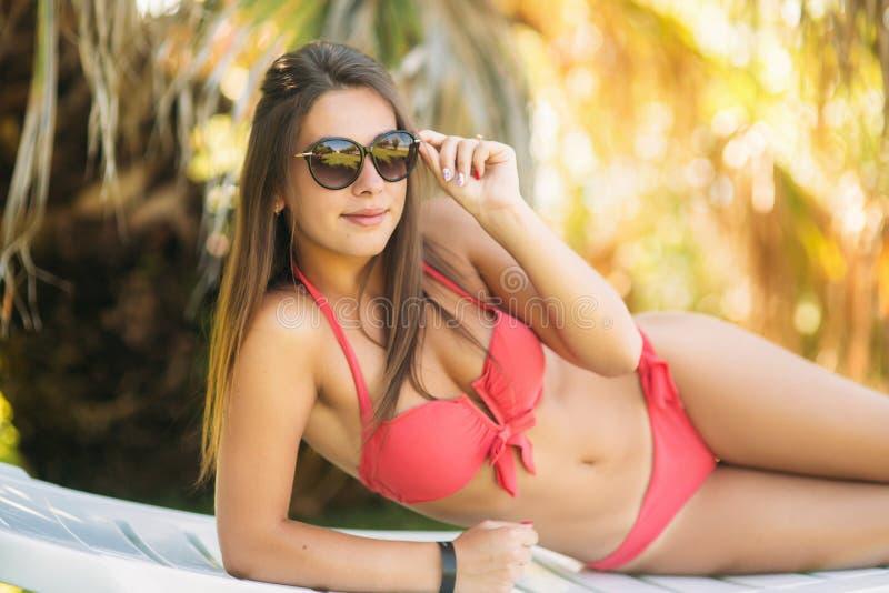 放松在轻便折叠躺椅的性感的年轻女人 说谎在海附近的桃红色比基尼泳装的美女 库存照片
