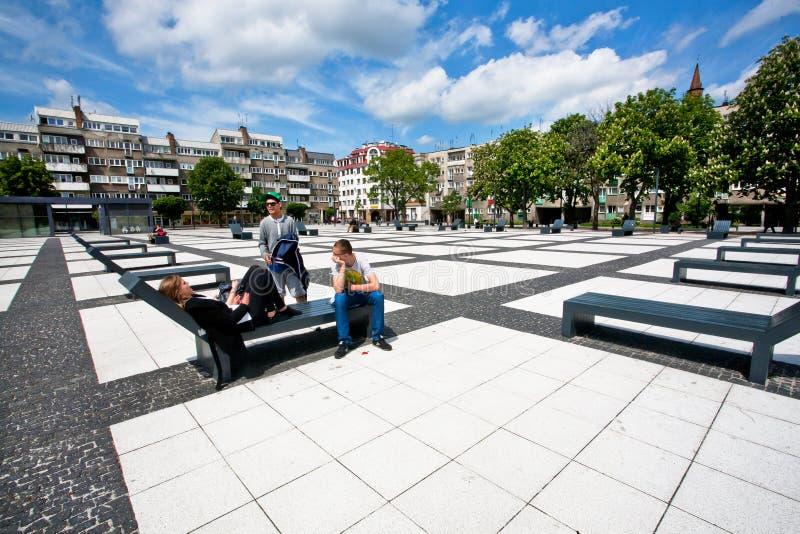 放松在都市样式城市的青年人停放在白色土块天空下 免版税库存照片
