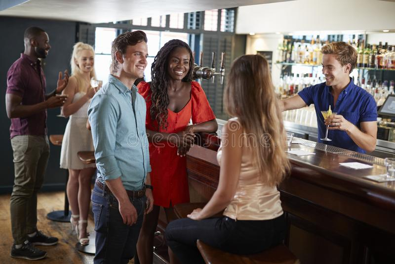 放松在酒吧的小组年轻朋友站立在柜台 图库摄影