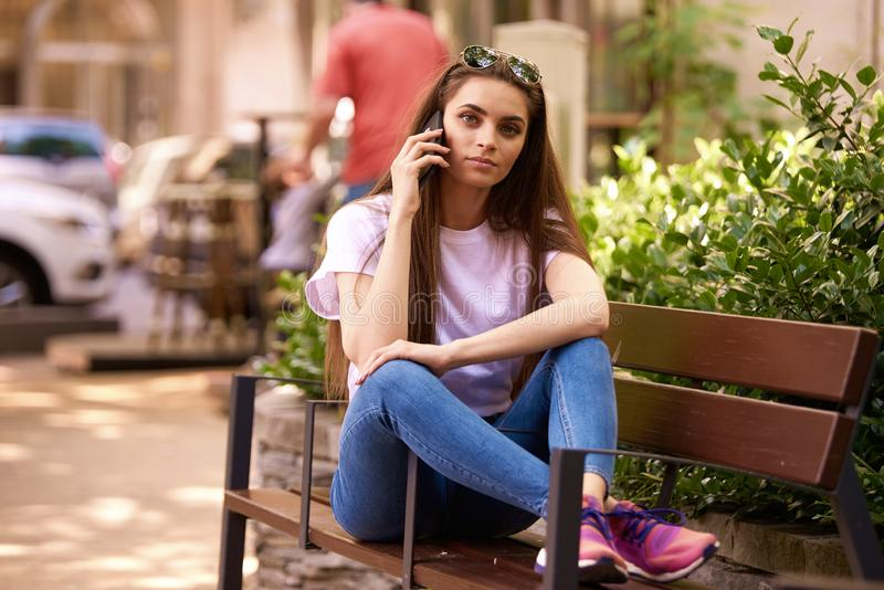 放松在长凳和打一次电话的美丽的年轻女人在城市 库存照片