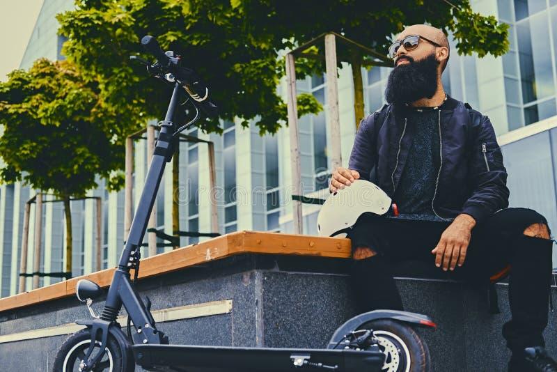 放松在长凳的一个人在乘坐乘电滑行车以后 免版税库存照片