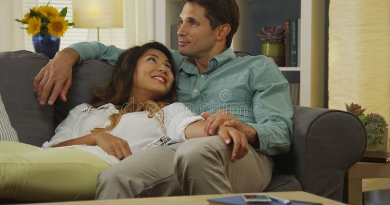 放松在长沙发的人种间夫妇 免版税库存图片