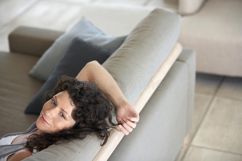 放松在长沙发的体贴的妇女 免版税库存图片