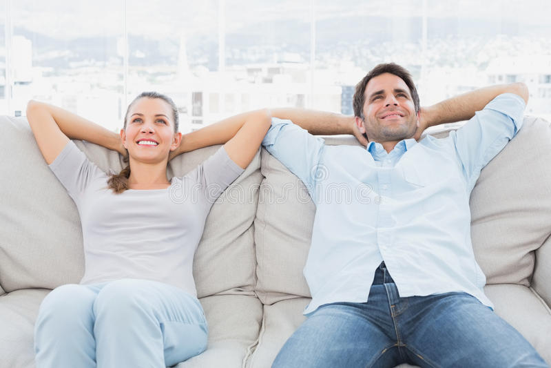 放松在长沙发的愉快的夫妇 库存图片