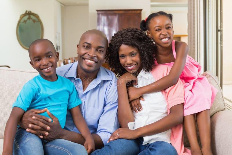放松在长沙发的愉快的家庭 图库摄影