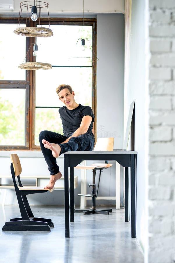 放松在顶楼样式公寓的一位年轻英俊的舞蹈家 图库摄影
