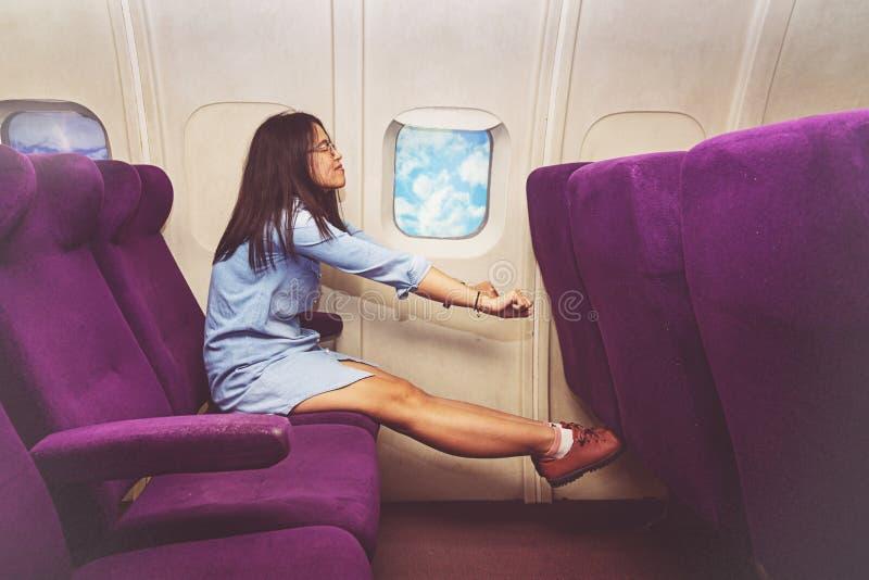 放松在飞机业务分类的亚裔妇女乘客  免版税库存照片