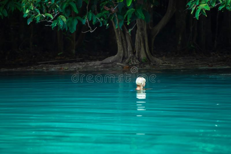 放松在鲜绿色水池的美丽的白肤金发的妇女画象在热带森林Sra Morakot,甲米府,泰国里 免版税图库摄影
