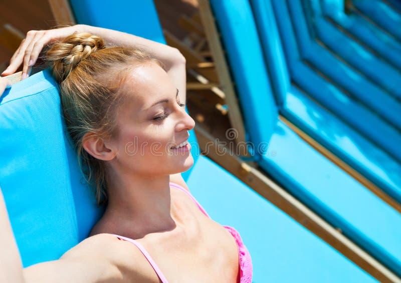 放松在轻便折叠躺椅的一桃红色比基尼泳装sweem的白肤金发的妇女 免版税库存图片
