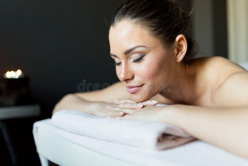 放松在黑暗的r的按摩桌上的年轻和美丽的夫人 免版税库存照片