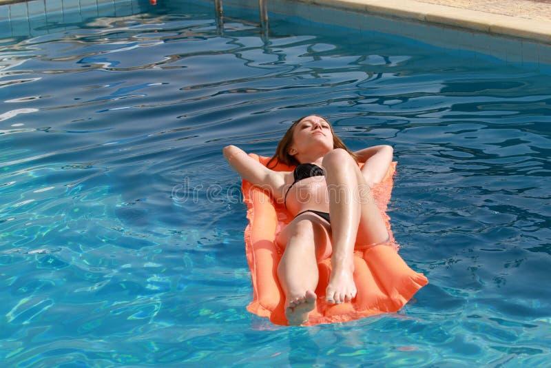 放松在水池的一个可膨胀的床垫的妇女 库存图片