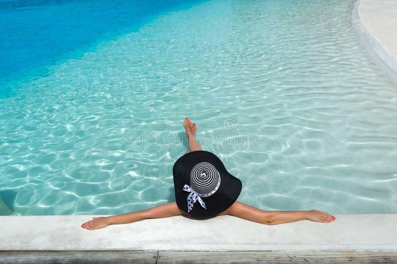 放松在水池的帽子的妇女