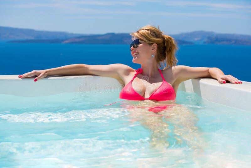 放松在水池的桃红色比基尼泳装的妇女 免版税库存图片