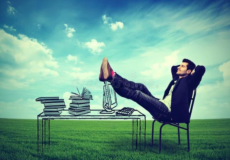 放松在他的书桌的商人户外在一个绿色草甸中间 免版税图库摄影