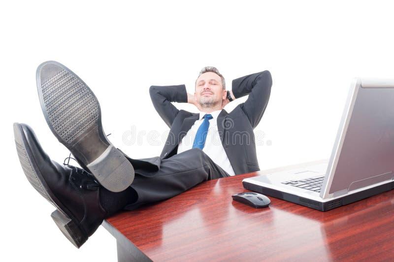 放松在他的办公室的年轻商人 库存图片