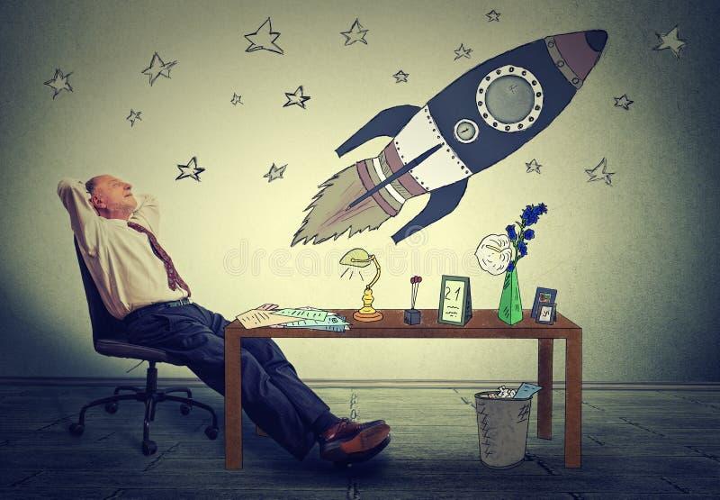 放松在他的在办公室作白日梦的书桌的商人太空游客 免版税库存图片