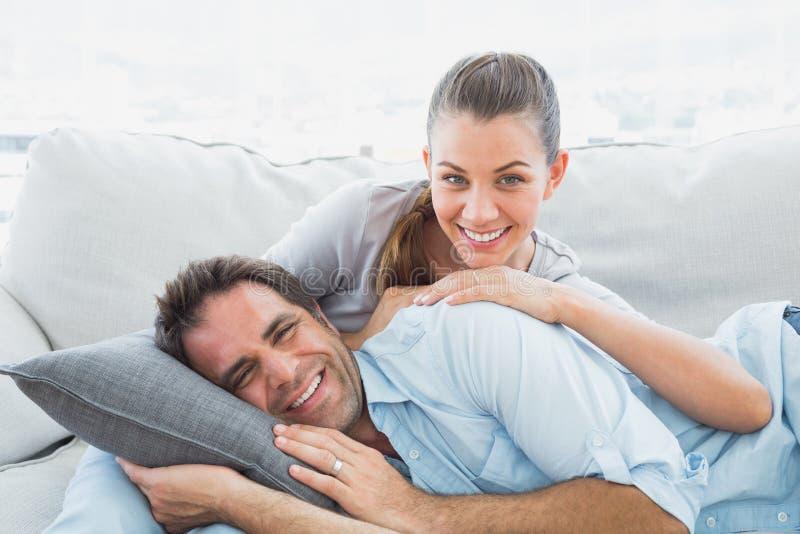放松在他们的沙发的愉快的夫妇微笑对照相机 库存图片