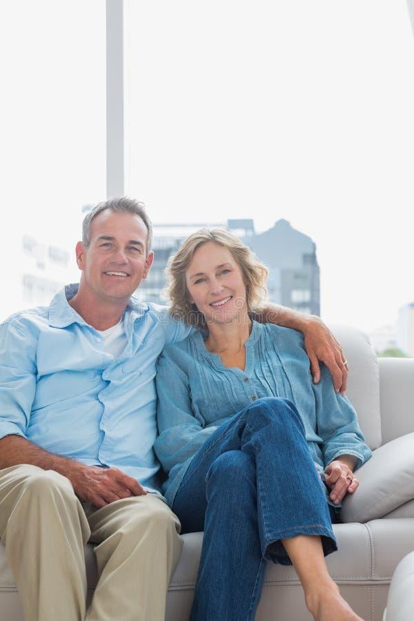 放松在他们的长沙发的快乐的夫妇 库存照片